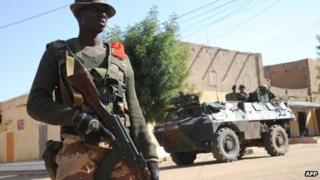 A Malian soldier stands guard as French soldiers patrols next to the central police station, on 11 February 2013 in Gao
