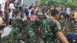 Rescuers search for the victims of a landslide in Manado, North Sulawesi, Indonesia, 17 February 2013