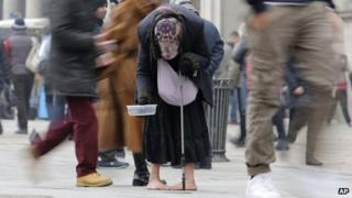 A woman begs for money amid passers by in central Milan, Italy, on 8 January 2013