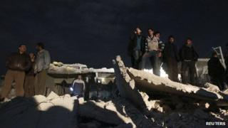 People gather at the site of what activists say was a Scud missile attack on Aleppo on 22 February 2013