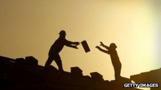 Construction workers pass bricks to each other in Phoenix, Arizona