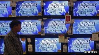 """A man walks past television screens showing an advertisement for a program on India""""s annual budget at an electronics shop in Mumbai in this February 22, 2013"""