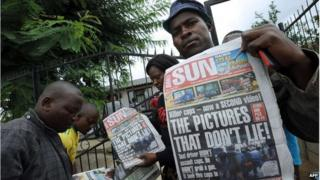 People hold up a newspaper outside the home of Mido Macia, Daveyton, South Africa