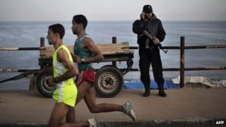 A picture taken on May 5, 2011 shows a Hamas policeman talking on the phone as Palestinian Olympic athlete Nader Masri (L) and a fellow runner speed along the waterfront in Gaza City
