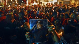 Supporters of Venezuelan President Hugo Chavez shout slogans outside the Military Hospital in Caracas on Tuesday evening after hearing of their leader's death
