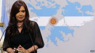 Cristina Fernandez standing in front of a map of the Falklands with the Argentine flag superimposed on it