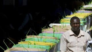 An unidentified man walks past stacked ballot boxes waiting to have their votes tallied, at a vote tallying centre in Nairobi, Kenya - Tuesday 5 March 2013
