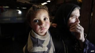 A Syrian woman carries her two-year-old grandson Mohammed at a refugee camp in the Bekaa valley in Lebanon