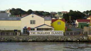 Shot of houses with a Welcome to the Falkland Islands sign in front
