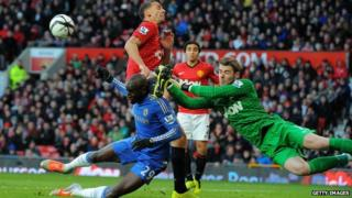 Chelsea's Demba Ba tackling with Manchester United's goalkeeper David de Gea and Manchester United's Rio Ferdinand