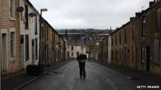An unemployed youth walks through a street in Accrington, Lancashire