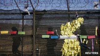 South Korean soldiers patrol past ribbons bearing peace messages arranged in the shape of the Korean peninsula near the demilitarized zone (DMZ) on 11 March 2013