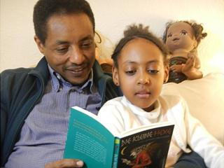 Mekonnen Mesghena reads The Little Witch with his daughter