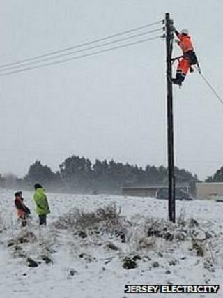 Jersey Electricity engineer up an overhead cable fixing it after heavy snowfall and strong winds