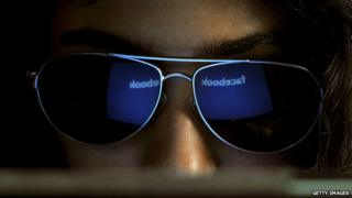 Facebook website reflected in the sunglasses of an India woman