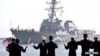 The guided missile destroyer USS Lassen (DDG 82) arrives as South Korean navy sailors wave South Korean and US flags at a South Korean naval port in Donghae, about 190km (118 miles) east of Seoul, 9 March 2013
