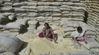 Women labourers collect wheat at a warehouse in Punjab
