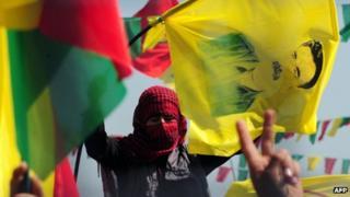 Demonstrators gesture and hold Kurdish flags