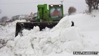 A tractor clears a road on the Isle of Man