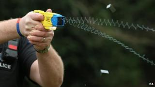 Police officer demonstrating the use of a Taser weapon