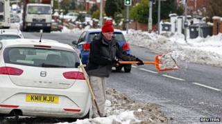 Man clears snow from his car in North Belfast