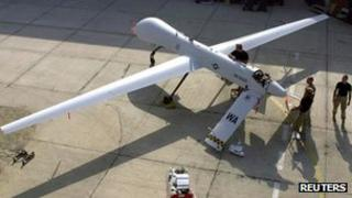 Members of the 11th Reconnaissance Squadron from Indian Springs, Nevada perform pre-flight checks on a Predator unmanned aerial vehicle prior to a mission in this November 9, 2001 file photo shot at an undisclosed location.