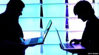 Two men using laptops