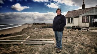Bryony Nierop-Reading stands on the cliff edge next to her Happisburgh home