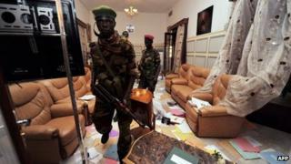 Seleka rebels look around the pillaged office of deposed president Francois Bozize in Bangui on March 28, 2013.
