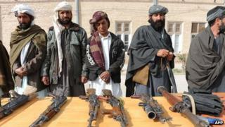 Former Taliban fighters display their weapons after joining Afghan government forces during a ceremony in Herat