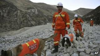 Rescuers lead sniffer dogs while searching through rock and debris at a gold mine after a mudslide in Gyama village, in Maizhokunggar County of Lhasa, Tibet, 30 March 2013