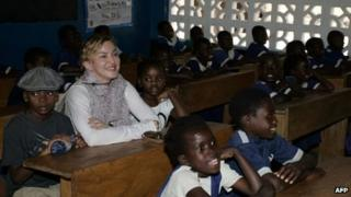 US pop star Madonna (2nd L) sits on April 2, 2013 with the two children she adopted in Malawi, David Banda (L) and Mercy James (3rd R), in a classroom at the Nkoko Primary School