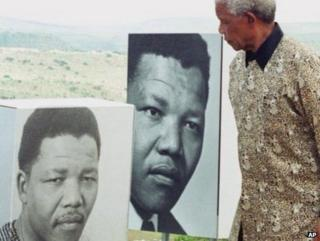 Mr Mandela passing portraits of himself in his youth, at the opening of a museum, Friday February 11 2000 in Mvezo, Eastern Cape (right)