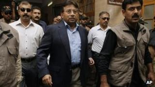 Former Pakistani President Pervez Musharraf, center, surrounded by guards arrives in a court in Karachi, Pakistan on Friday, March 29, 2013.
