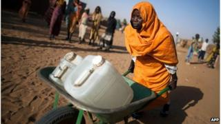 Sudanese woman pushing jerry cans of water in a camp for displaced people, Darfur, March 2013