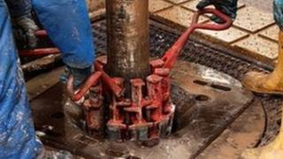 Engineers work on drilling platform at fracking facility