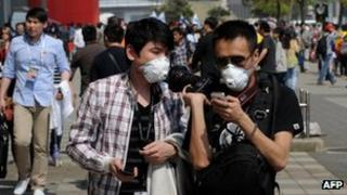 People wear facemasks due to the recent outbreak of bird flu as fans arrive before the start of the Formula One Chinese Grand Prix in Shanghai on 14 April 2013