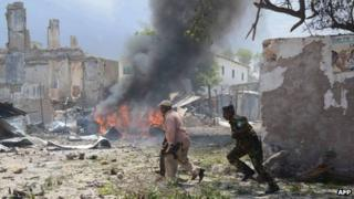 Somali police run after a suicide attack in Mogadishu on 14 April 2013