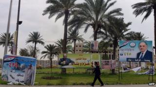 An Iraqi walks past campaign billboards in Baghdad