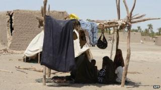 Pakistani earthquake survivors sit in a makeshift shelter in the quake hit Mashkail area of southwestern Baluchistan province