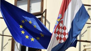 Croatian and European Union flags hang from a government building in Zagreb