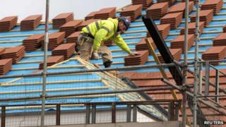 A builder works on the roof of a new residential property in north London