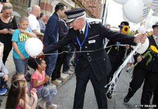 Policeman hands out balloons in Manchester