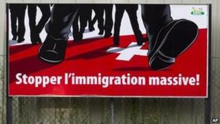 """A poster of the right-wing Swiss People's Party (SVP) which shows feet walking on the Swiss cross and the message """"Stop mass immigration"""" (2 Aug 2011)"""