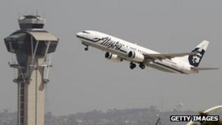 Plane takes off past an air traffic control tower in Los Angeles, California 22 April 2013