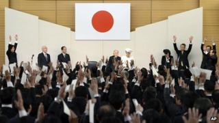 Japan's Prime Minister Shinzo Abe (top left) and attendees cheer in front of Emperor Akihito (C) and Empress Michiko (C)