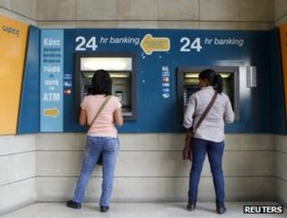 Women withdraw cash from machines in Nicosia, Cyprus, 30 April