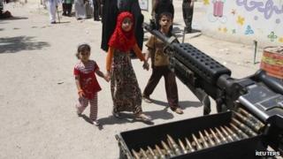 Children walk past a machine-gun in Baghdad (20 April 2013)