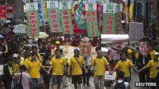 Local and striking dock workers chant slogans during a protest calling for legislative restrictions on standard working hours, on Labour Day in Hong Kong, 1 May 2013