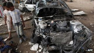 Iraqi boys inspect site of car bomb attack in Baghdad on 16 April